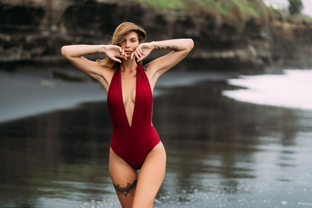 Photo for Sexy model with big breasts in a red swimsuit poses on black sand beach. - Royalty Free Image