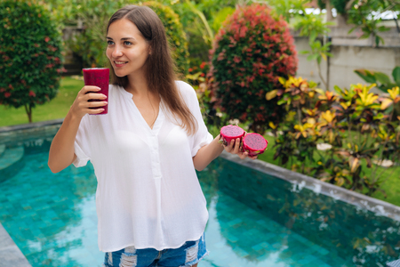 Photo pour Portrait of beautiful young girl holding glass of dragon fruit smoothie and fruit in her hands near pool. - image libre de droit