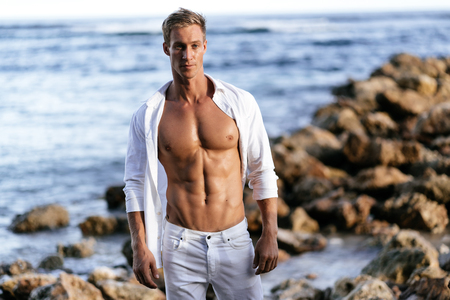 Photo pour Muscular athletic sexy man in white shirt with bare-chested rests on beach - image libre de droit