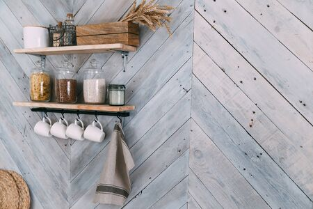 Photo pour Spices in glass jars on shelf, white cups, towel hang on hooks on kitchen wall - image libre de droit