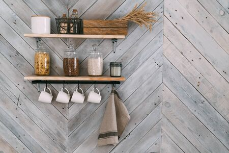 Photo pour Cereals in glass jars on shelf, white cups, towel hang on hooks on kitchen wall - image libre de droit
