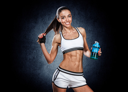 young beautiful sports girl posing with a bottle in his hand