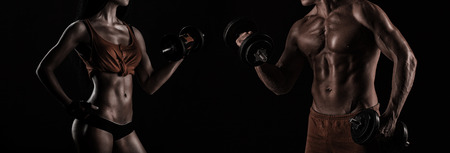 Foto de handsome young muscular couple doing exercises with dumbbells - Imagen libre de derechos