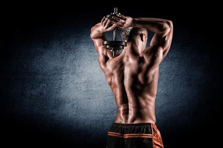 Foto de strong and handsome young man doing exercise with dumbbells - Imagen libre de derechos