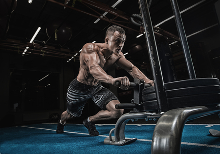 sled push man pushing weights workout exercise at gym