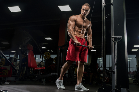 Foto de Muscular man working out in gym doing exercises at triceps, strong male naked torso abs - Imagen libre de derechos