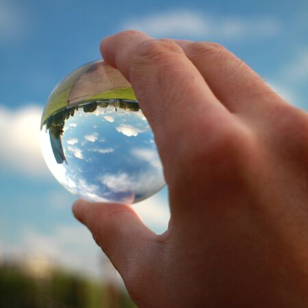 Photo pour glass crystal ball in hand and city reflection on summer sunny day against beatiful blue cloudy sky - image libre de droit