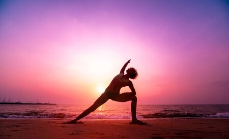 Foto de Beautiful young woman practic yoga at the beach. Early morning exercise. Sunrise. Palms background - Imagen libre de derechos