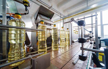 Photo pour Bottling line of sunflower oil in bottles. Vegetable oil production plant. - image libre de droit