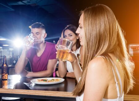 Photo for Cheerful friends in the pub. Drinking beer, talking, having fun. - Royalty Free Image
