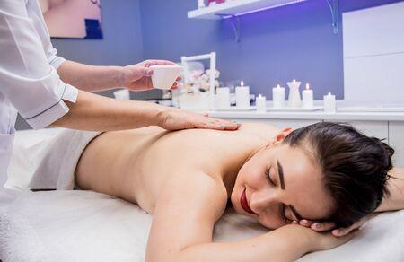 Photo pour Beautiful young woman enjoying massage in spa salon. Cosmetology - image libre de droit