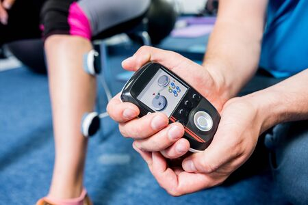 Photo pour Physical therapist install electrostimulator on the muscles of the legs. - image libre de droit