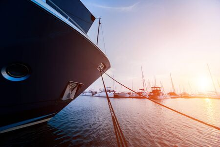 Photo pour Beautiful view of marina and harbor with yachts and motorboats. Sunset at the ocean. Background - image libre de droit