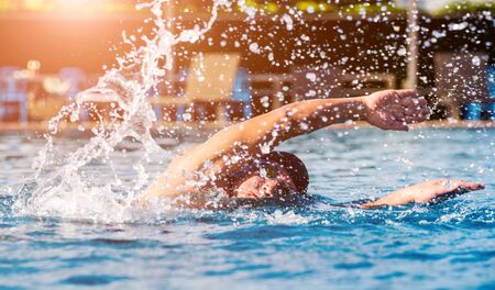 Photo pour Young athletic man swimming in the swimming pool. Active sport - image libre de droit