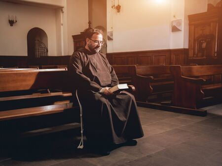 Photo pour A monk in robes with holy bible in their hands praying in the church - image libre de droit