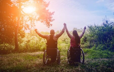 Foto de Handicapped couple resting in the forest near lake. Wheelchairs in the forest on the natural background. Camping. Summertime - Imagen libre de derechos