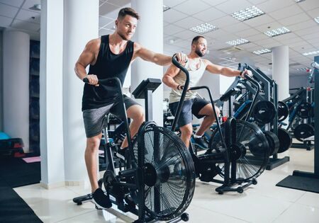 Photo pour Young men with muscular body using air bike for cardio workout - image libre de droit
