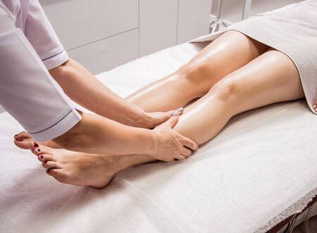 Photo pour Beautiful young woman enjoying foot massage in spa salon. Cosmetology - image libre de droit