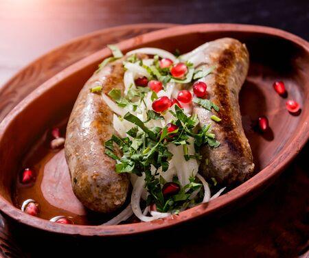 Photo pour Grilled sausage in a clay pot. Georgian restaurant. - image libre de droit