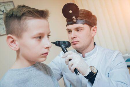 Photo pour Doctor examines boy ear with otoscope. Medical equipment. - image libre de droit
