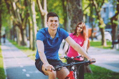 Photo pour Cycling young couple. In the park. Beautiful bicycle lane. - image libre de droit