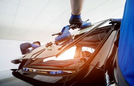 Photo for Automobile special workers replacing windscreen or windshield of a car in auto service station garage. Background - Royalty Free Image