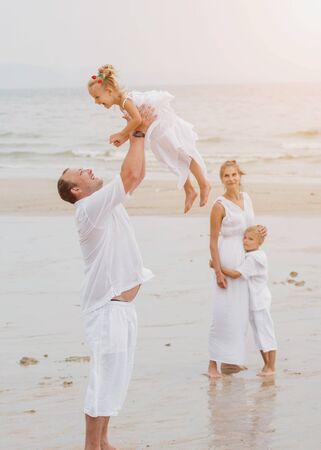 Photo for Happy young family on the sunset at the beach. - Royalty Free Image