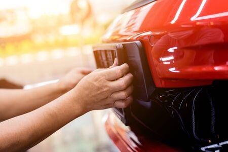 Photo pour Technician changing car plate number in service center. - image libre de droit