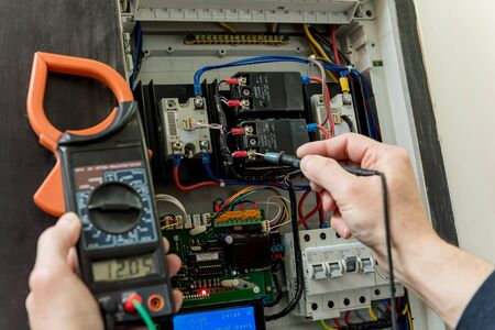 Photo pour The man is repairing the switchboard voltage with automatic switches. - image libre de droit