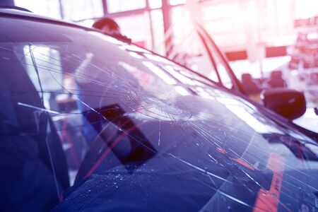 Photo for Automobile special workers remove old windscreen or windshield of a car in auto service station garage. Background - Royalty Free Image