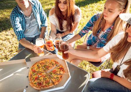 Photo pour Cheerful friends on picnic in the park. Eating pizza - image libre de droit