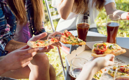 Photo for Cheerful friends on picnic in the park. Eating pizza - Royalty Free Image