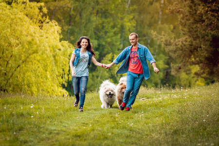 Photo for Young couple with the dogs in the park - Royalty Free Image