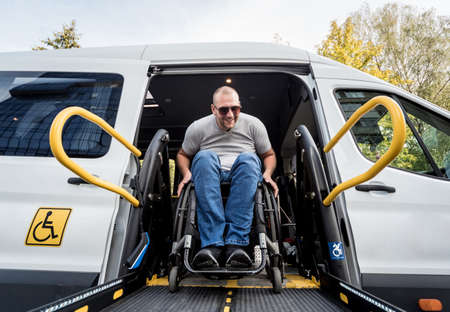Photo for A man in a wheelchair on a lift of a vehicle for people with disabilities - Royalty Free Image
