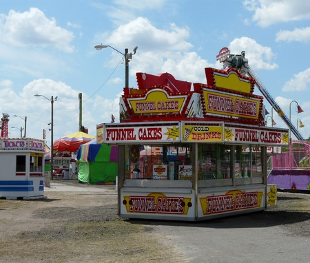 Concession stand, ticket booth, rides, and games at the county fair on a beautiful day.