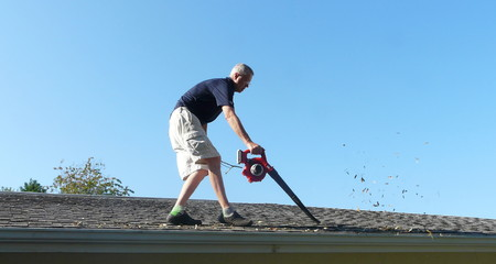 Photo pour A homeowner is on the roof of his residence using a leaf blower to remove leaves from the gutter in preparation for storm season water runoff. - image libre de droit