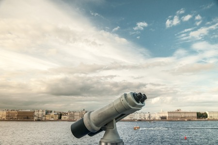 Tower viewer turned towards Neva river in Saint-Petersbourg, Russia. Tourist destionations image. Sightseeing binocular against blurred background of city at dawn in light of sunset.