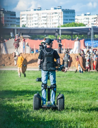 MOSCOW - JUNE 06, 2015: Cameraman on Steadiseg shooting historical reenactment in Kolomenskoye, Moscow. Steadiseg is easy way to capture smooth tracking shots at a fairly brisk pace.
