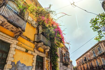 Facade of the Old Italian House with Balcony Decorated with Fresh Flowers