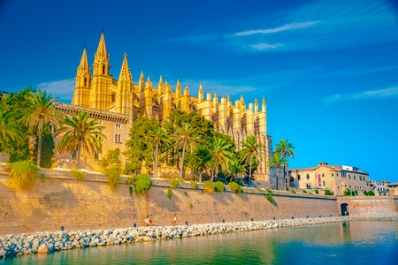 Foto de Cathedral of Palma de Mallorca, rear view from road. Big gothic church on the sea shore. Beautiful travel picture of Spain. - Imagen libre de derechos
