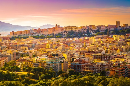 Photo pour Sunset on Cagliari, panorama of the old city center with traditional colored houses with beautiful yellow-pink clouds, Sardinia Island, Italy - image libre de droit