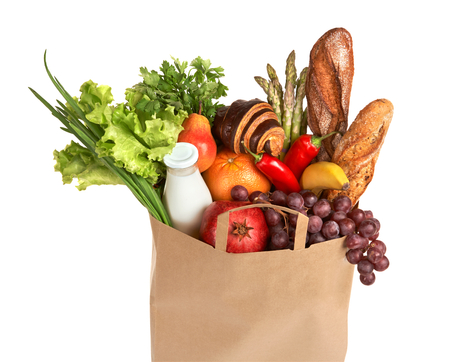 A grocery bag full of healthy fruits and vegetables - studio photography of assorted foods in brown grocery bag isolated over white background