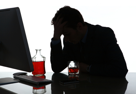 Silhouette of alcoholic drunk young man  photo of businessman addicted to alcohol at the workplace, depression and crisis concept