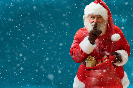 Santa Claus with huge red sack keeping forefinger by his mouth and looking at camera Merry Christmas New Year's Eve concept Closeup on blurred blue background.