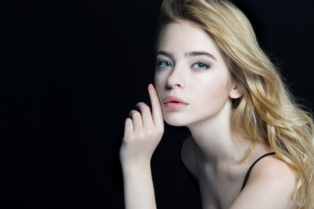 Beautiful Girl face. Perfect skin. Close-up of an attractive girl of European appearance on dark background.の写真素材