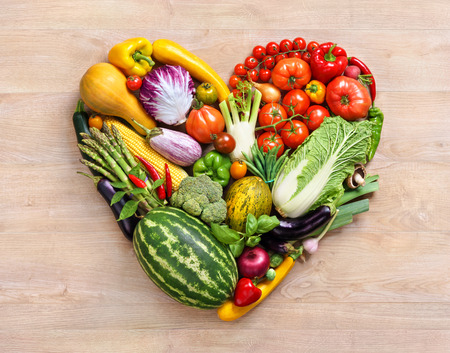 Heart symbol. Fruits diet concept. Healthy eating concept food photography of heart made from different fruits and vegetables on old wooden table