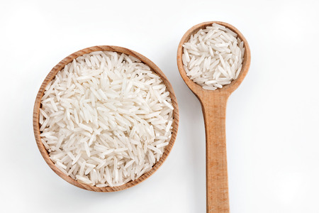 Rice in wooden spoon and bowl on white background.  Top view