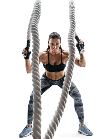 Strong muscular woman working out with heavy ropes. Photo of attractive woman in sportswear isolated on white background. Strength and motivation.