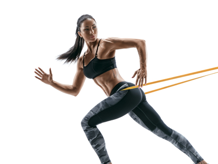 Strong woman using a resistance band in her exercise routine. Young woman performs fitness exercises on white background.
