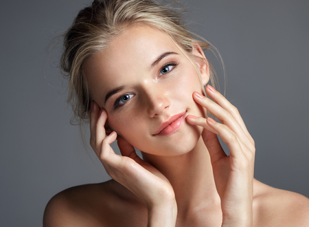 Photo pour Attractive young girl touching her lips. Photo of blonde girl with perfect skin on grey background. Beauty & Skin care concept - image libre de droit